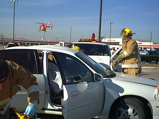 Fire fighters attempt to free a person from an automobile accident